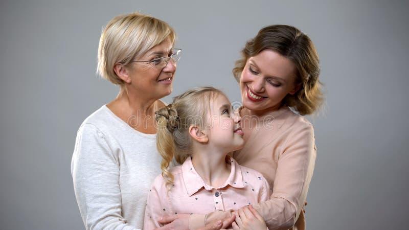 Abuela, hija y nieto abrazando en el fondo gris, relaciones de la confianza foto de archivo