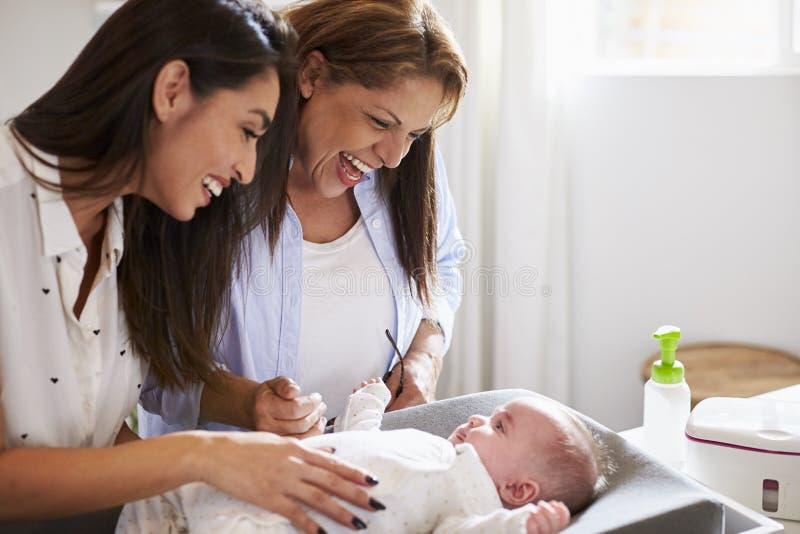 Abuela hispánica joven e hija adulta que juegan con su hijo del bebé en la tabla cambiante, cierre para arriba foto de archivo