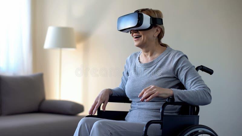 Abuela impresionada en las gafas que llevan de la silla de ruedas, jugando al juego de VR, dispositivo imágenes de archivo libres de regalías