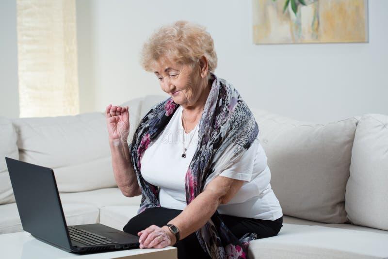 Abuela moderna que habla en Skype imagen de archivo