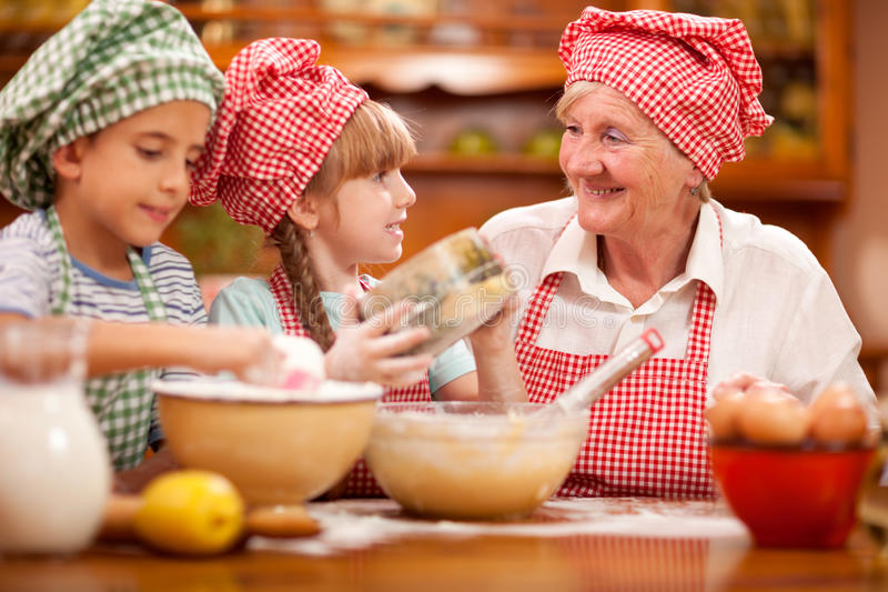Abuela, nieto y cocinero Baking In Kitchen de la nieta imagenes de archivo