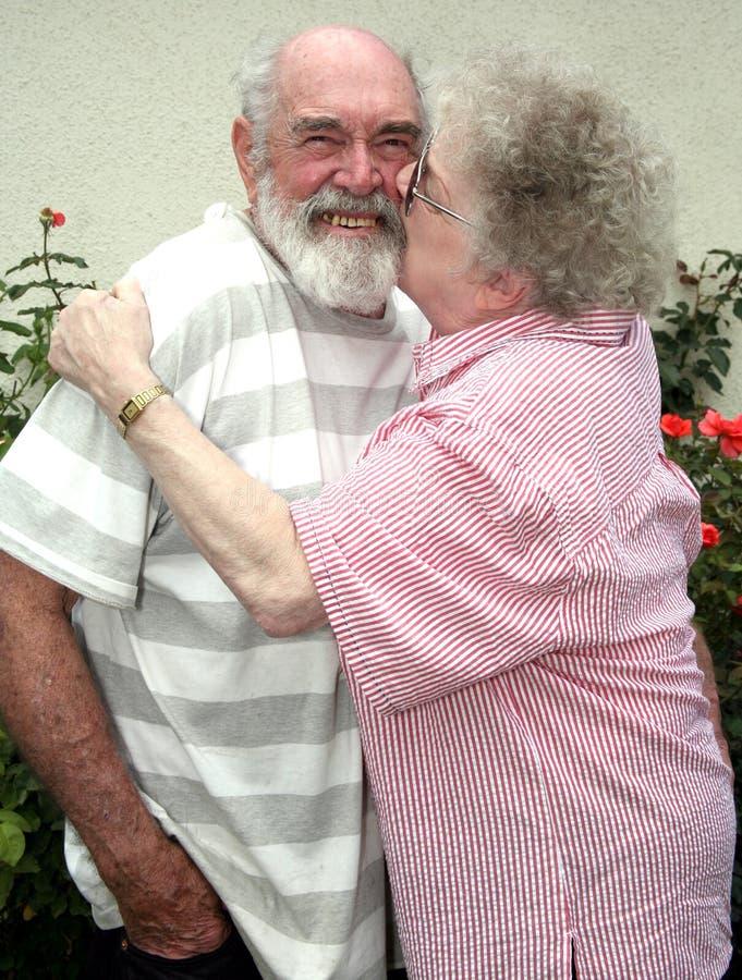 Abuela que besa al grandpa fotografía de archivo