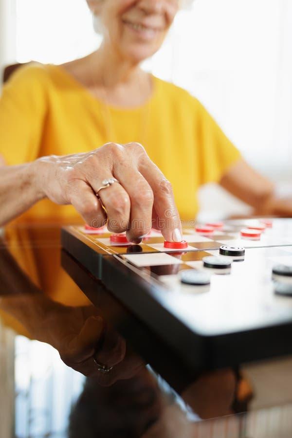 Abuela que juega al juego de mesa de los inspectores en hospicio fotos de archivo libres de regalías
