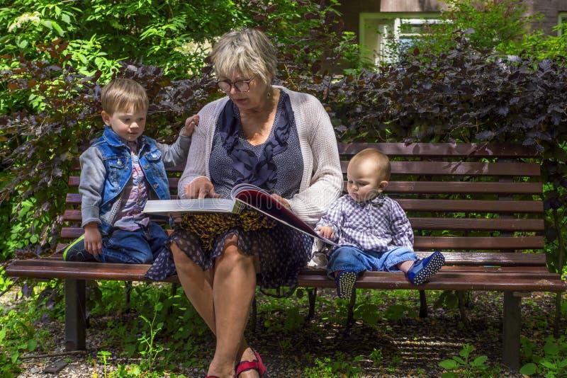 Abuela que lee a sus nietos imagen de archivo