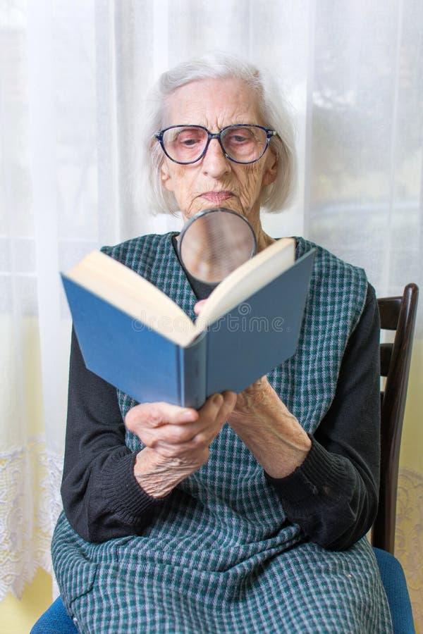 Abuela que lee un libro a través de la lupa imágenes de archivo libres de regalías