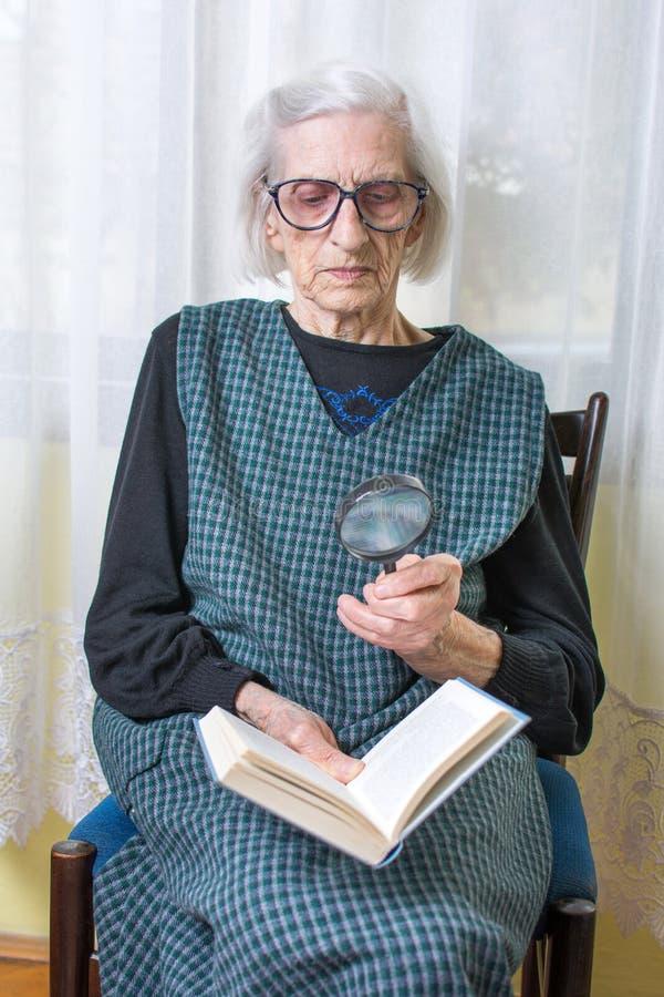 Abuela que lee un libro a través de la lupa fotos de archivo