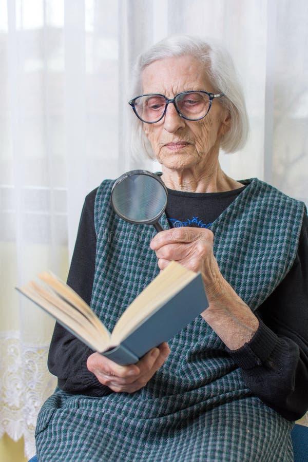 Abuela que lee un libro a través de la lupa imagen de archivo libre de regalías