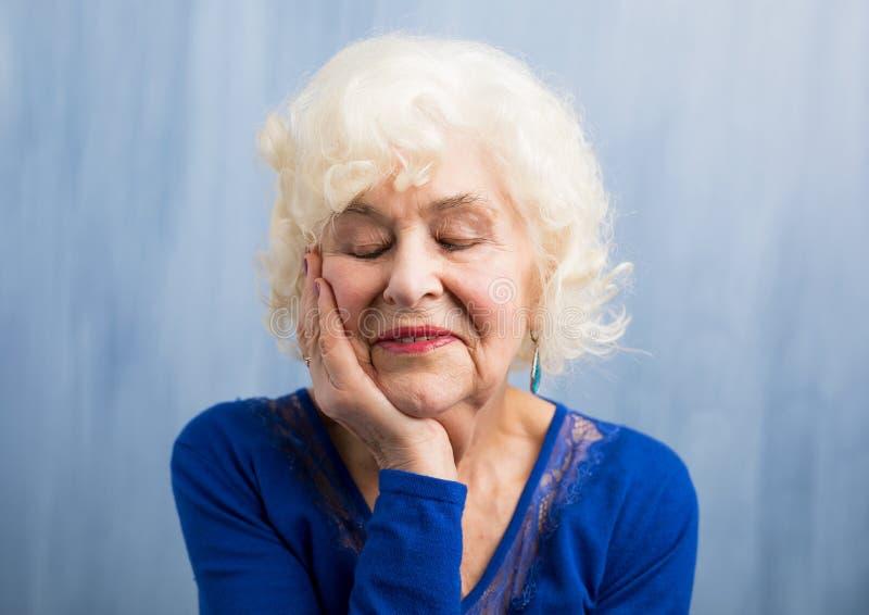 Abuela que lleva a cabo su mano cerca de su cara foto de archivo libre de regalías