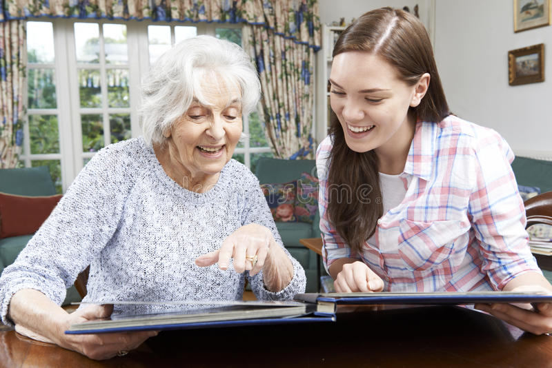 Abuela que mira el álbum de foto con la nieta adolescente imagen de archivo