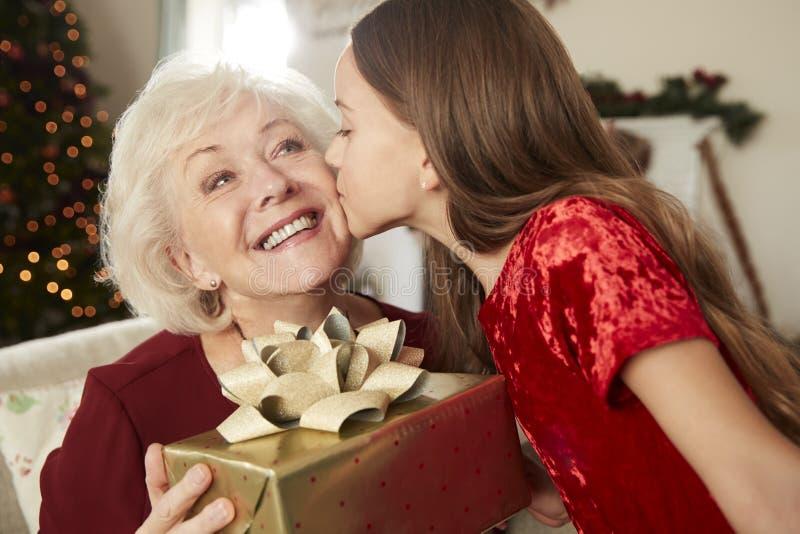 Abuela que recibe el regalo de la Navidad de nieta en casa fotos de archivo