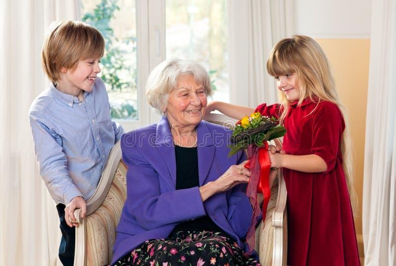 Abuela que recibe las flores de nietos imagen de archivo
