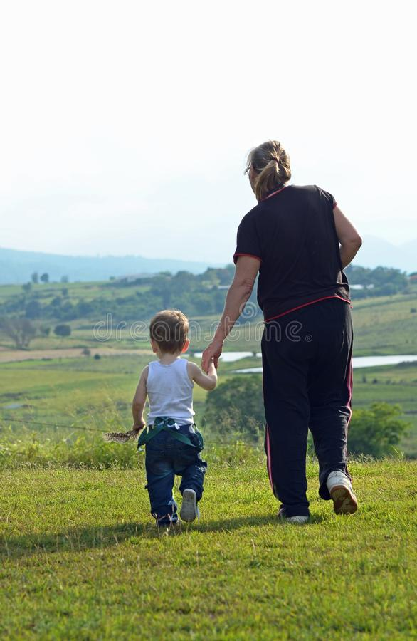 Abuela que toma el paseo del nieto en campo rural imponente fotografía de archivo libre de regalías