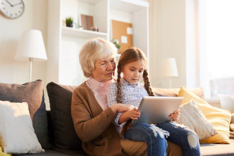 Abuela usando la tableta de Digitaces foto de archivo libre de regalías