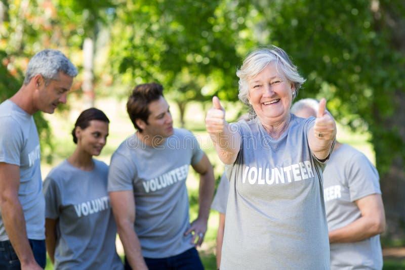 Abuela voluntaria feliz con los pulgares para arriba imágenes de archivo libres de regalías