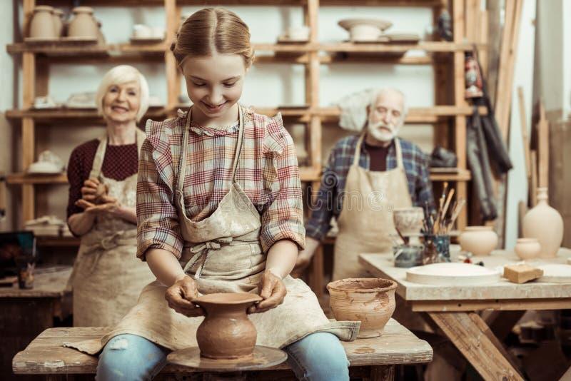 Abuela y abuelo con la nieta que hace la cerámica fotografía de archivo libre de regalías
