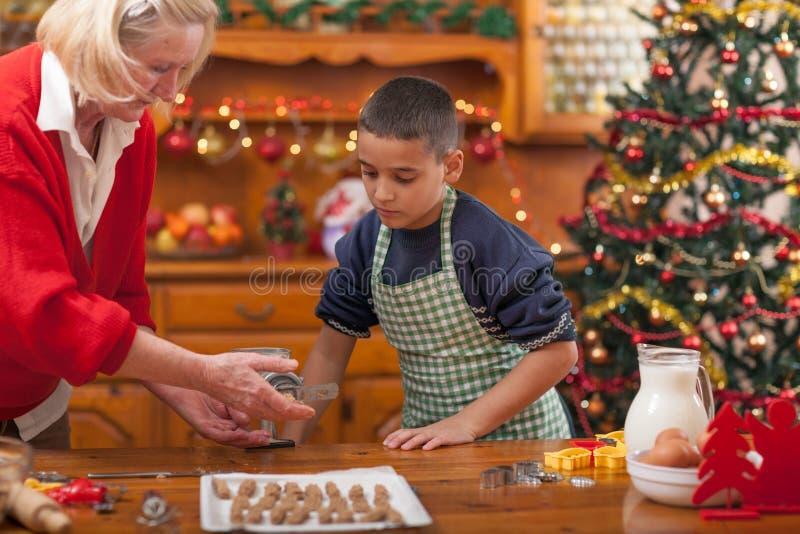Abuela y muchacho en la cocina que prepara las galletas de Navidad imágenes de archivo libres de regalías