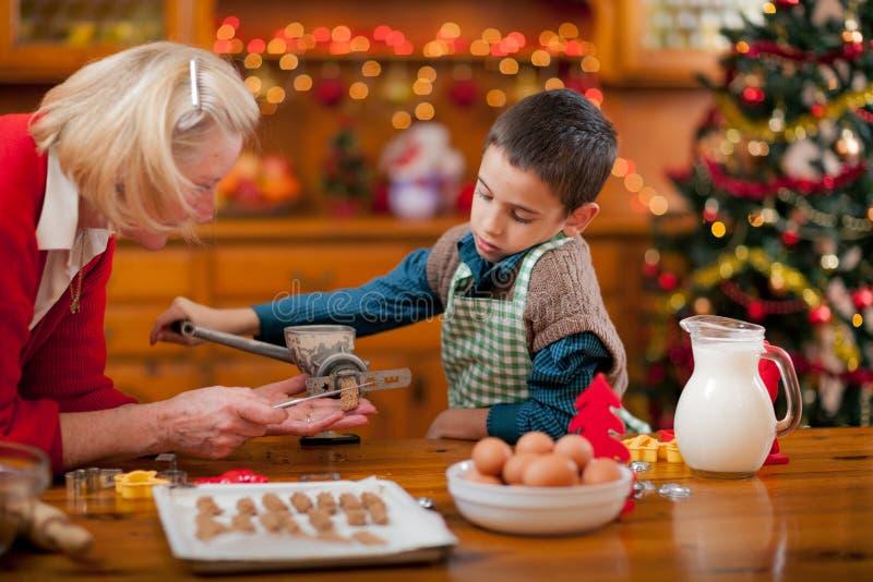 Abuela y niño pequeño en la cocina que prepara las galletas de Navidad fotos de archivo