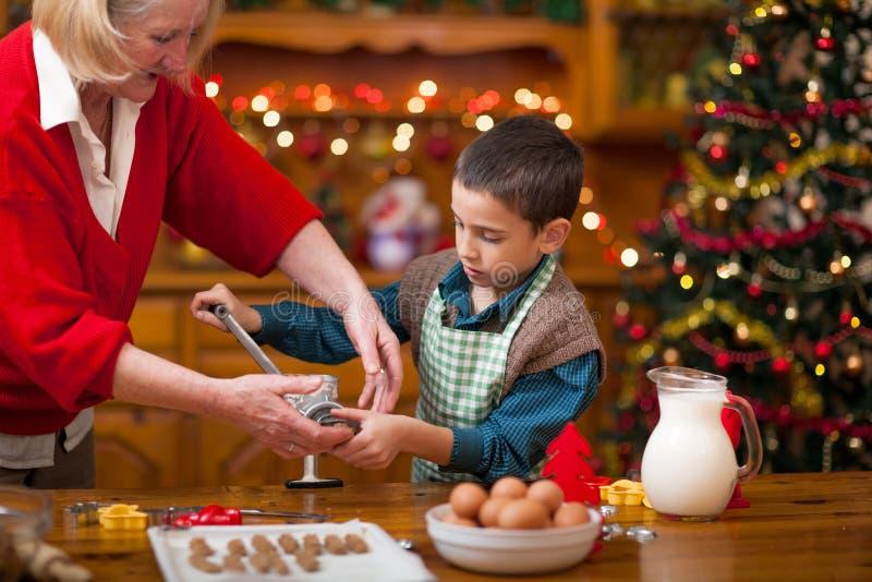 Abuela y niño pequeño en la cocina que prepara las galletas de Navidad imagen de archivo