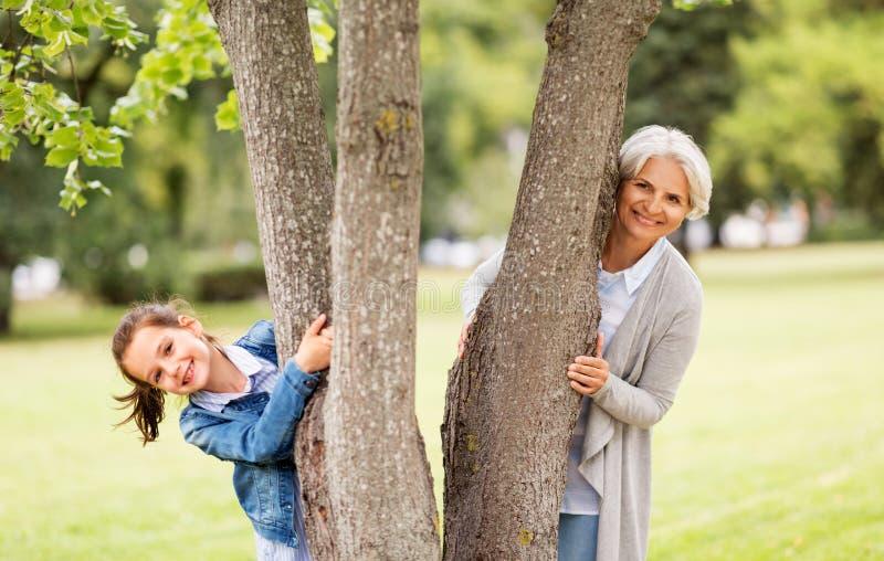 Abuela y nieta detrás del árbol en el parque imagen de archivo