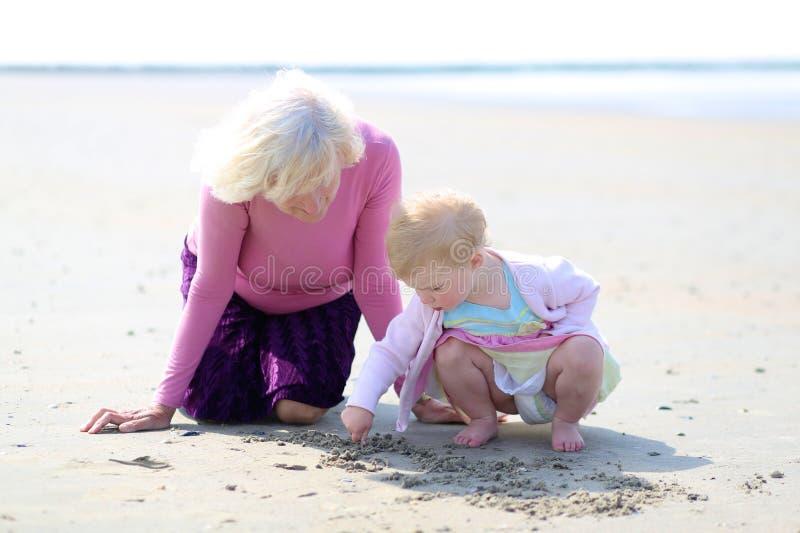 Abuela y nieta que juegan junto en la playa fotos de archivo libres de regalías