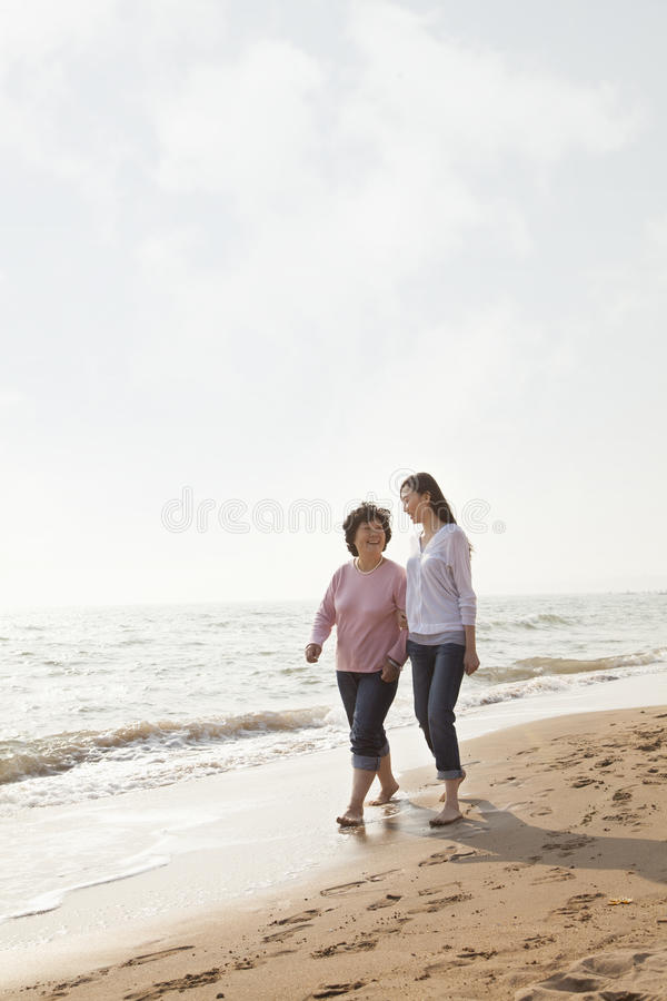 Abuela y nieta que toman un paseo por la playa imagen de archivo libre de regalías