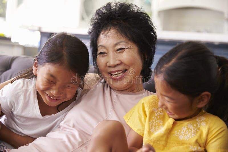 Abuela y nietas que se relajan en Sofa At Home imágenes de archivo libres de regalías