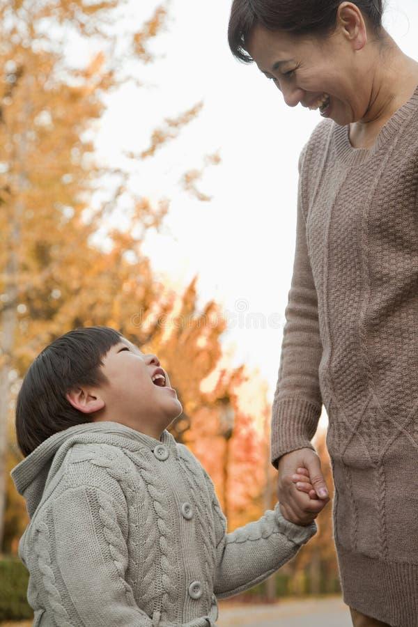 Abuela y nieto en el parque que celebra las manos y la sonrisa fotografía de archivo