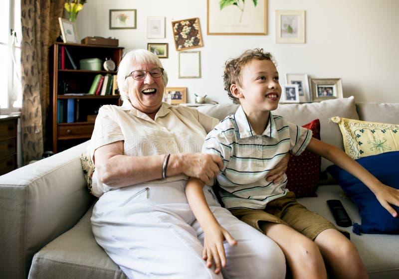 Abuela y nieto que se sientan en el sofá junto imagen de archivo