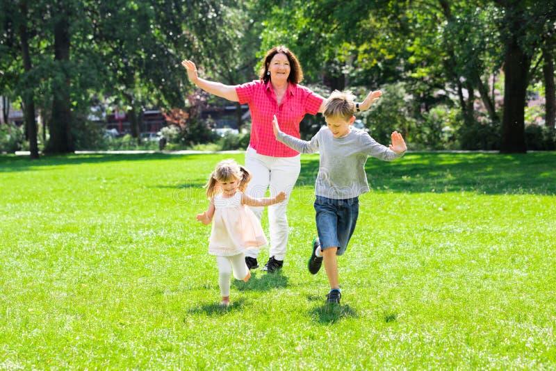 Abuela y nietos que corren en parque fotografía de archivo libre de regalías