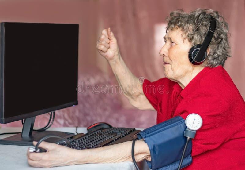 Abuelas en el mundo moderno de la alta tecnolog?a Las abuelas aman los juegos de ordenador imagen de archivo