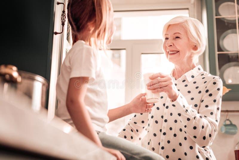 Abuelita buena que mira a su nieta con amor imagen de archivo
