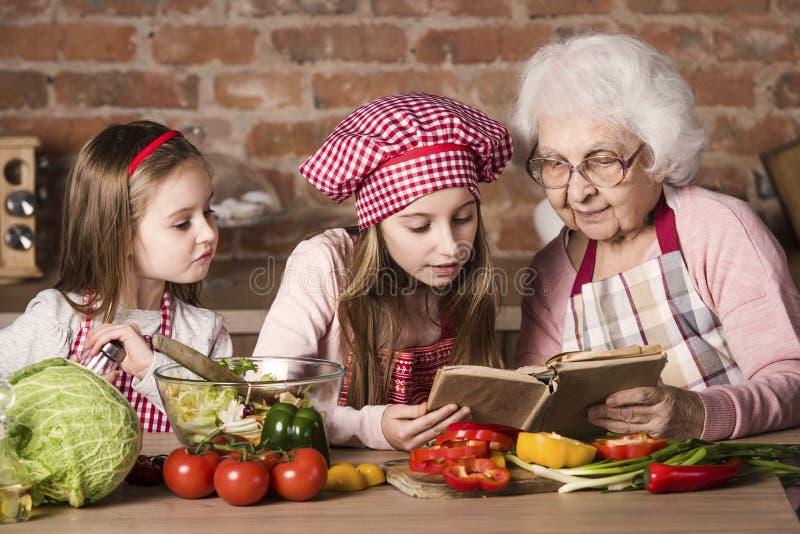 Abuelita con dos nietas que leen receta imagen de archivo
