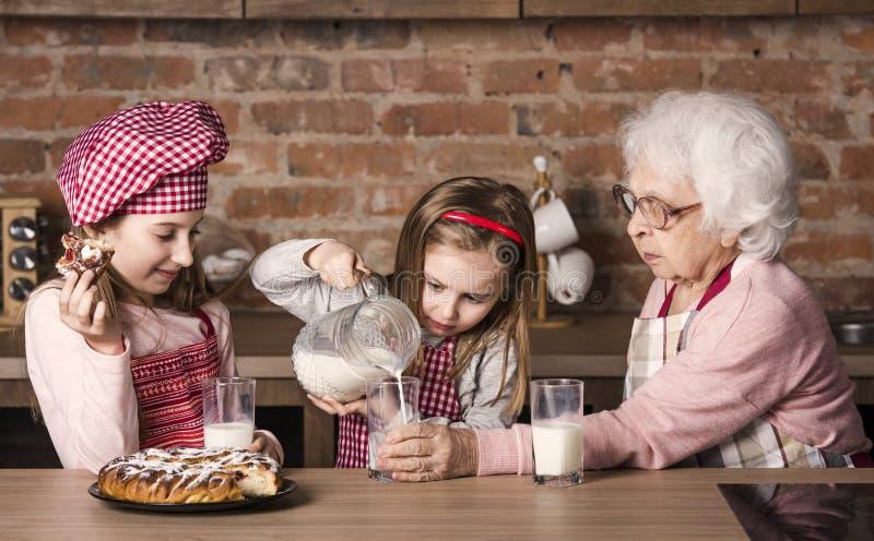Abuelita con dos pequeñas nietas que se sientan en la tabla en el kitche fotografía de archivo libre de regalías