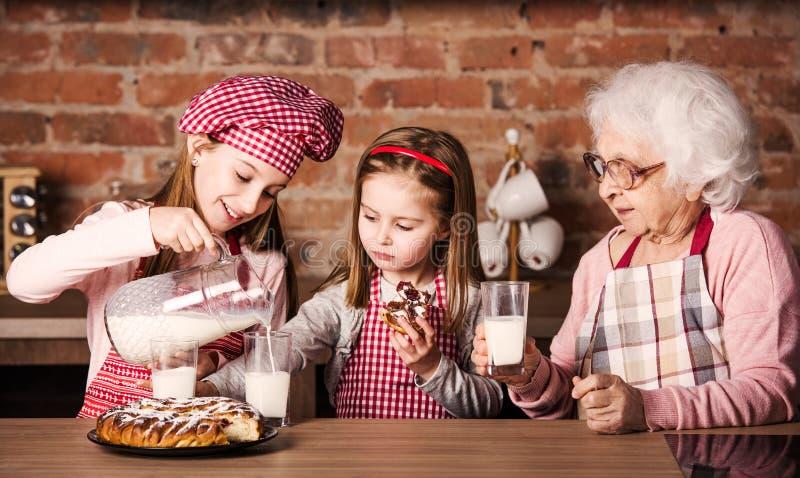Abuelita con las nietas tastying la empanada imagen de archivo