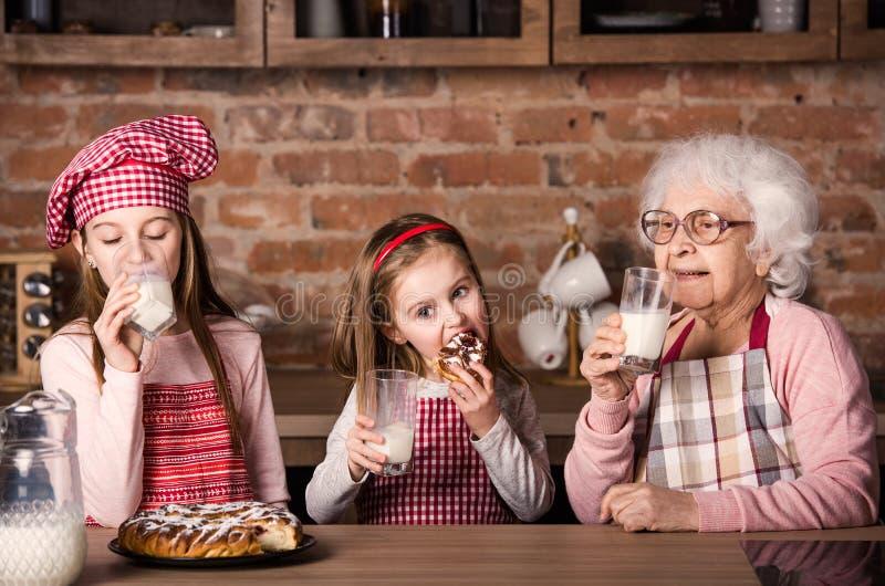 Abuelita con las nietas tastying la empanada foto de archivo libre de regalías