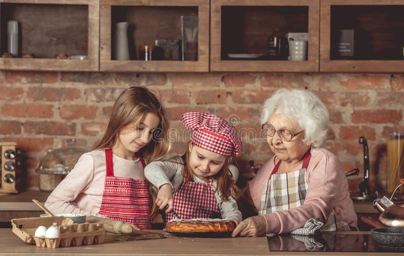Abuelita con sus nietas que prueban la empanada foto de archivo