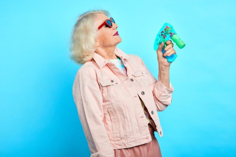 Abuelita divertida loca infantil que sostiene una pistola del juguete, jugando con ella fotografía de archivo