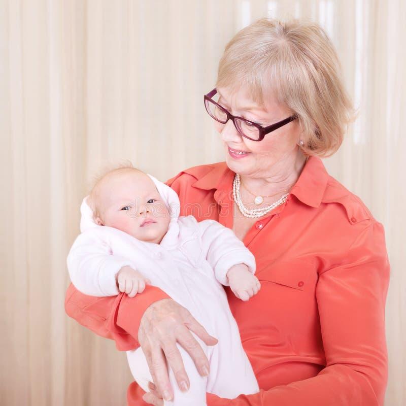 Abuelita feliz que detiene al niño recién nacido fotos de archivo libres de regalías