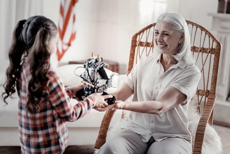 Abuelita interesada sonriente que toma el robot de las manos de las nietas fotos de archivo
