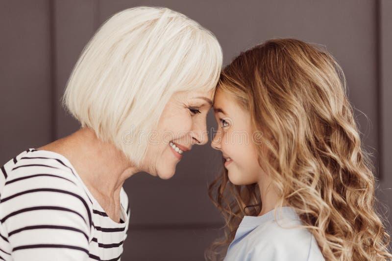 Abuelita y nieta que tocan sus frentes, vista lateral foto de archivo libre de regalías