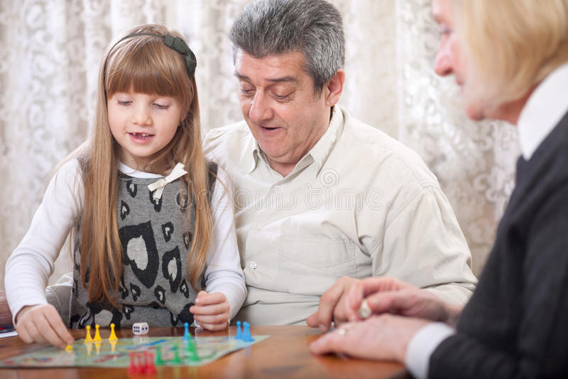 Abuelo, abuela y nieta sonrientes jugando al tablero foto de archivo libre de regalías