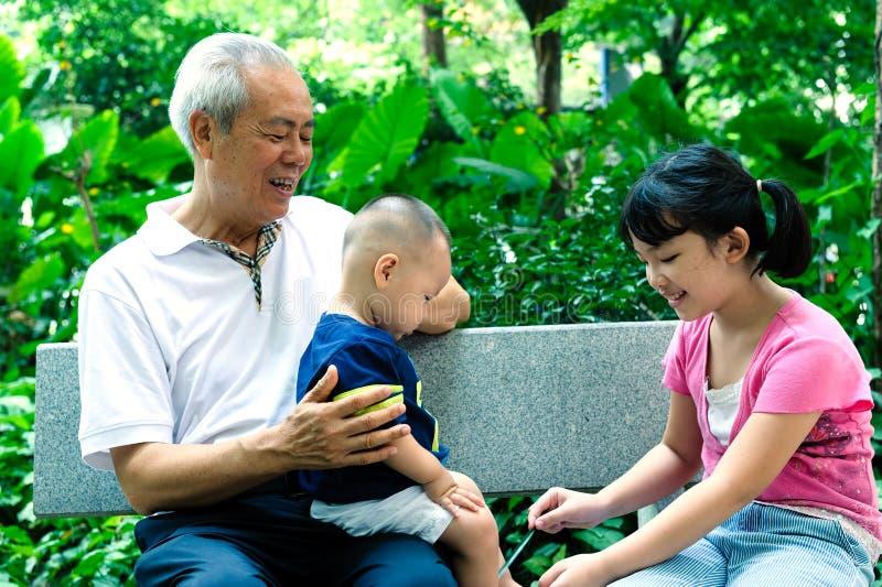 Abuelo asiático con dos foto de archivo libre de regalías