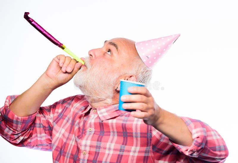 Abuelo barbudo del hombre con el casquillo del cumpleaños y la taza de la bebida Partido loco del cumpleaños Celebraciones del cu fotografía de archivo