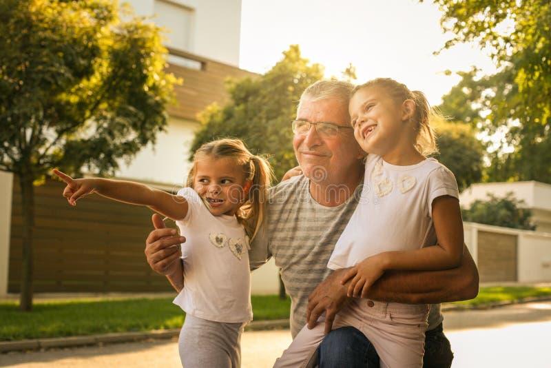 Abuelo con sus nietas en la calle que mira algo trasero foto de archivo