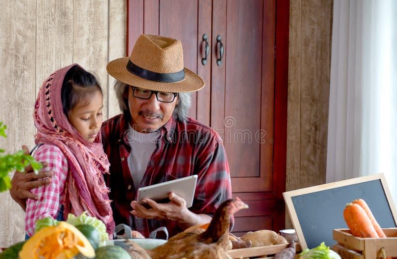 Abuelo del viejo hombre con el sombrero explicar sobre su menú para cocinar a su nieto usando la tableta en la cocina imágenes de archivo libres de regalías