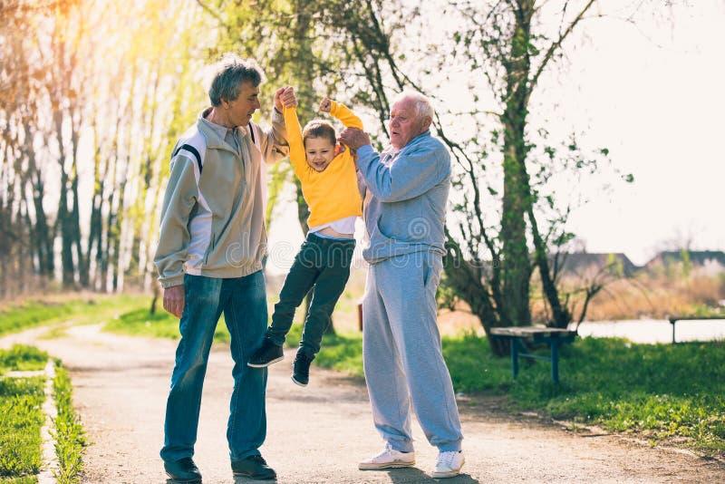 Abuelo dos que camina con el nieto en el parque fotografía de archivo libre de regalías