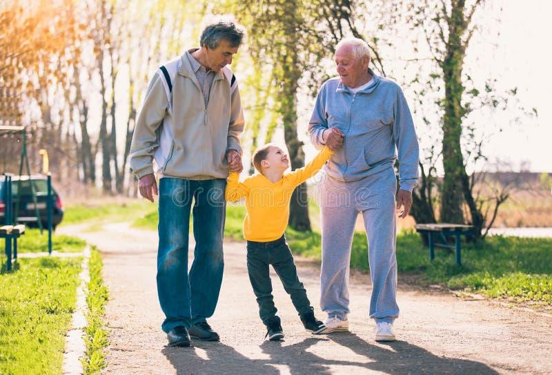 Abuelo dos que camina con el nieto en el parque imagen de archivo
