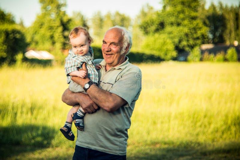 Abuelo feliz con el niño, sosteniéndose encendido los brazos fotografía de archivo libre de regalías