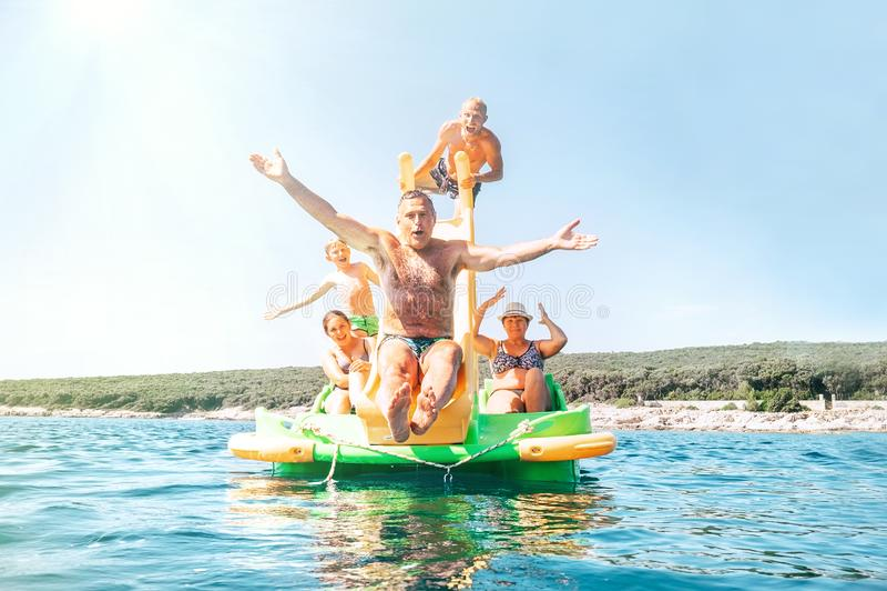 Abuelo feliz de la familia que resbala abajo con las manos para arriba en el catamarán flotante de la diapositiva del patio como  fotografía de archivo