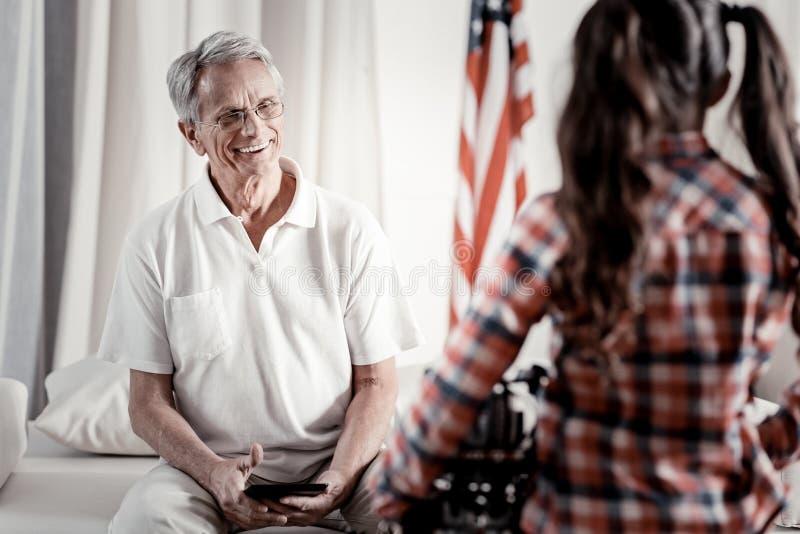 Abuelo moderno alegre que sonríe en la nieta fotografía de archivo libre de regalías